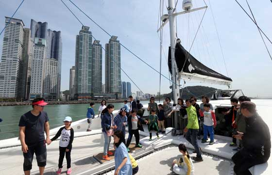 해양레저 무료체험행사에 참가한 나들이객들이 요트를 타고 광안대교와 마린시티 경관을 보고 있다.  (사진=저작권자(c) 연합뉴스, 무단 전재-재배포 금지)