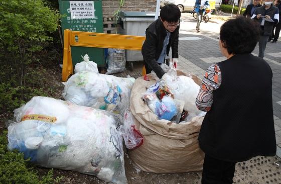 한 아파트에서 공동주택 분리배출 위반 여부를 점검하고 있는 단속반원들과 주민들의 모습.(사진=저작권자(c) 연합뉴스, 무단 전재-재배포 금지)