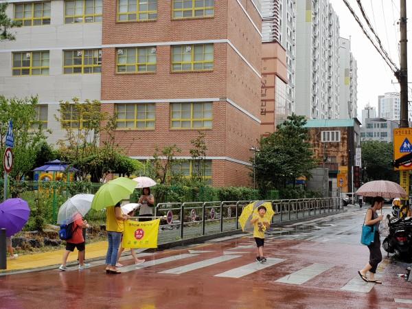 어린이 교통안전지킴이의 지도에 따라서 횡단보도를 건너는 초등학생들