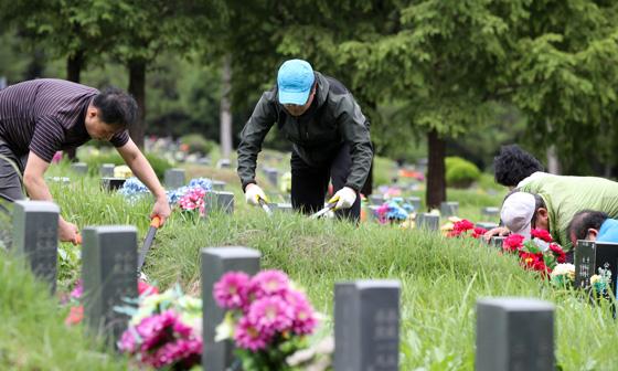 추석 연휴가 앞두고 성묘객들이 조상 묘에 벌초를 하고 있다(사진=저작권자(c) 연합뉴스, 무단 전재-재배포 금지).