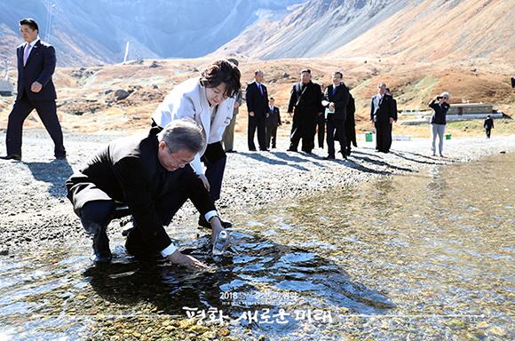 문재인 대통령이 20일 오전 김정은 국무위원장과 백두산 천지를 산책하던 중 천지 물을 물병에 담고 있다. ⓒ 평양사진공동취재단