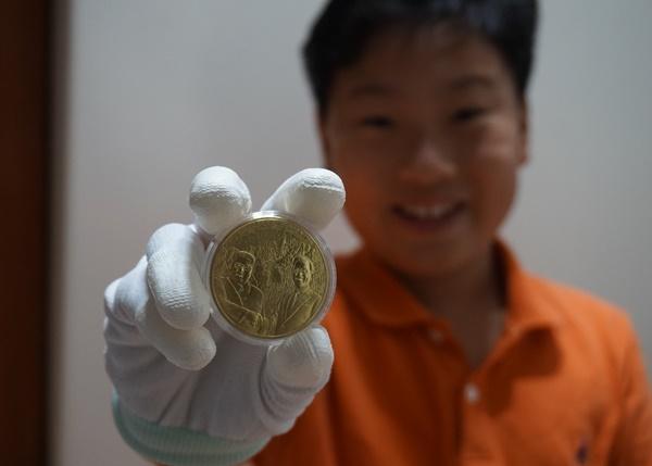 (한반도 평화 기념메달 황동화 앞면을 보이며 미소짓고 있는 황찬우군)