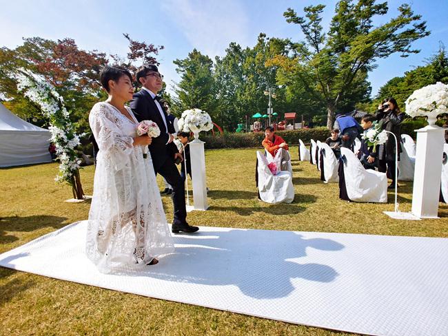 가족들과 함께 고른 웨딩드레스를 입은 권옥현씨 부부가 버진로드를 걷고있다