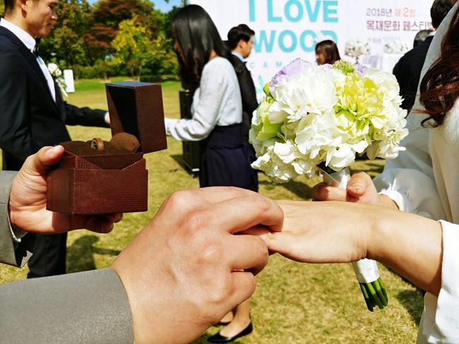 목혼식에 참석한 부부가 직접 만든 나무반지를 교환하고 있다