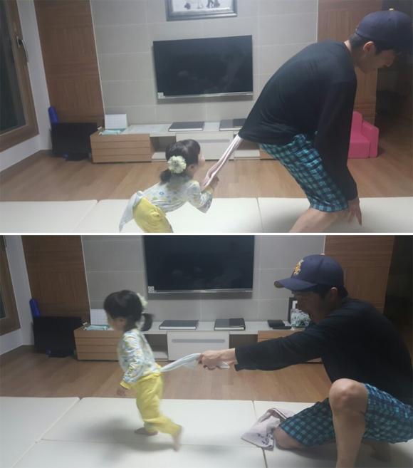 집안에서 쉽게 활용할 수 있는 수건으로 꼬리잡기 놀이 중인 김태규씨와 딸 꽃송이의 모습.