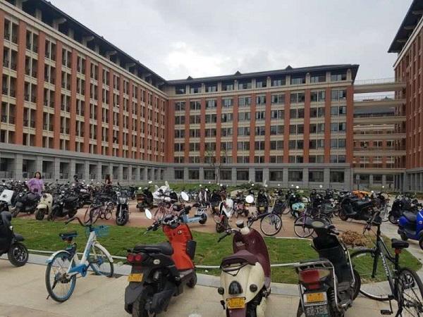 중국의 대학교 기숙사 앞에 늘어서 있는 공유자전거와 전동차들.
