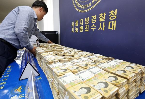 지난해 서울경찰청 지능범죄수사대(지수대)에서 경찰 관계자가 불법 스포츠 도박 사이트를 운영한 일당으로부터 압수한 현금을 진열하고 있다.(출처=뉴스1)
