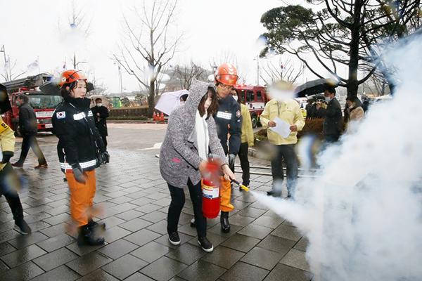 '화재 대피 훈련'에서 국민들이 소화기 사용법을 익히고있다.