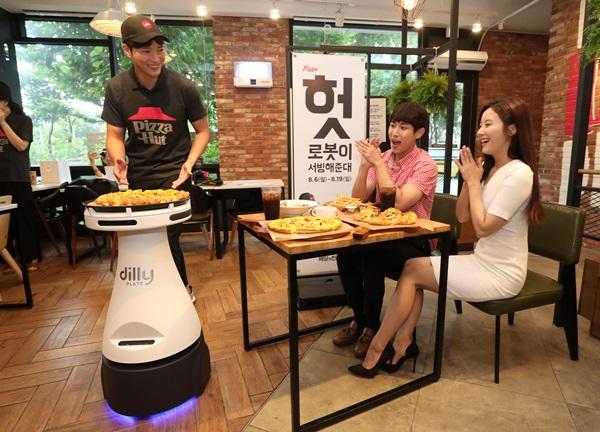 한국 피자헛-배달의민족 업계 최초 서빙로봇 '딜리 플레이트' 도입 행사 모습.(출처=뉴스1)