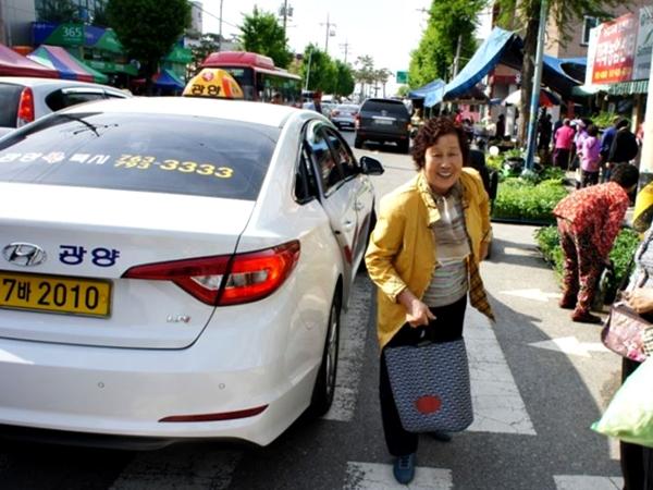 100원 택시를 타고 시장에 나온 어르신이 밝게 웃고 있다.(출처=광양시)