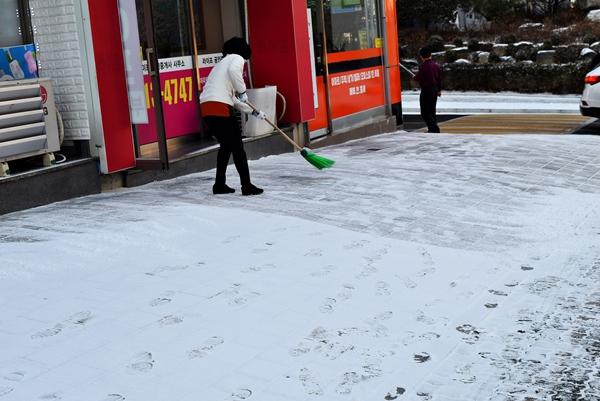 경기도 성남시 분당구에서 한 주민이 상가 앞의 눈을 치우고 있다.