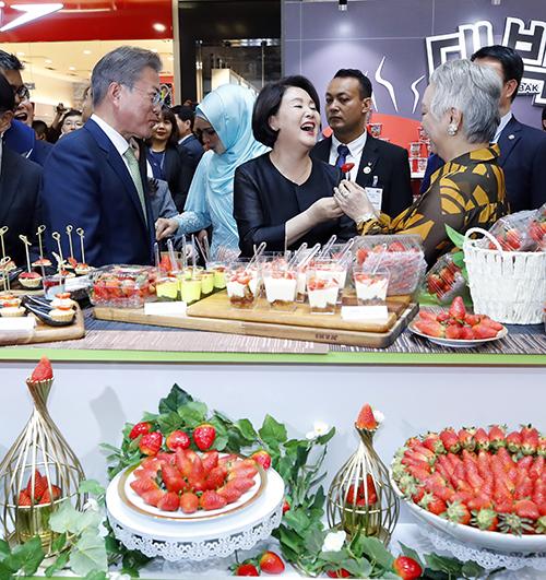 말레이시아를 국빈 방문 중인 문재인 대통령과 부인 김정숙 여사가 12일 오후 말레이시아 쿠알라룸푸르 최대 쇼핑센터인 원우타마 쇼핑센터에서 열린 '한·말레이시아 한류-할랄 전시회'에서 한국산 딸기 부스를 방문해 한국에서도 유명한 '원 서머 나이트 (ONE SUMMER NIGHT)'을 부른 가수 진추하 씨에게 딸기를 권하고 있다. (사진=저작권자(c) 연합뉴스, 무단 전재-재배포 금지)