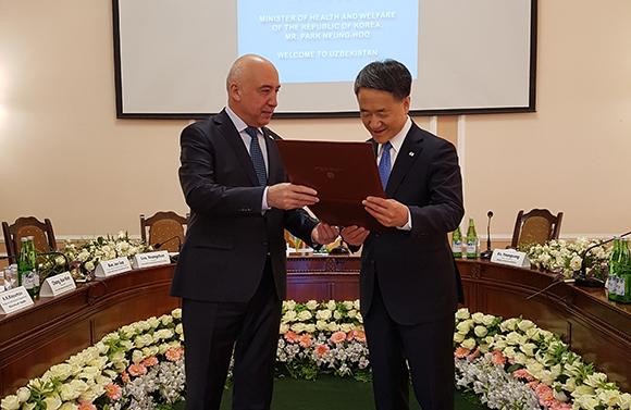 박능후 보건복지부 장관이 우즈베키스탄 보건부로부터 공로패를 받고 있다.(사진=보건복지부)