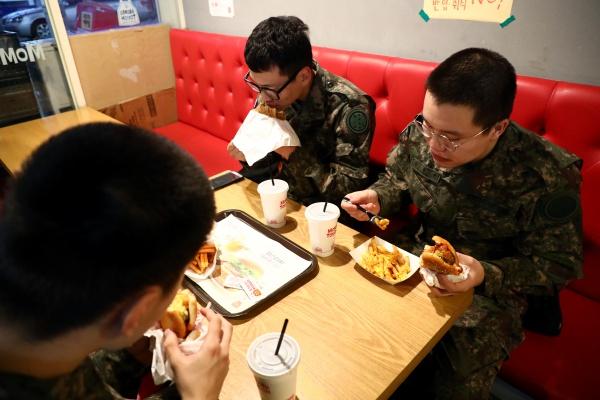병사 평일 외출 제도 전면시행 첫날인 1일 오후 강원 화천군 화천읍에서 병사들이 일과를 마치고 외출을 나와 햄버거를 먹고 있다.