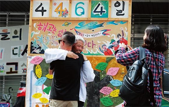 콜텍 노사 조인식이 열린 4월 23일 서울 강서구 콜텍 본사 앞에서 42일간 단식한 임재춘 조합원(가운데)이 축하인사를 받고 있다.(사진=한겨레)