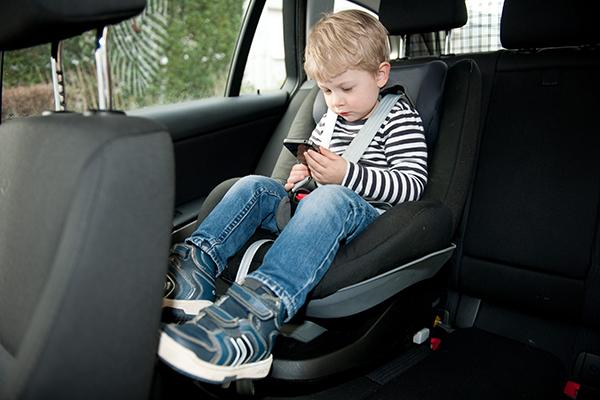 카시트에 앉은 아이가 스마트폰을 보고 있다. (사진=저작권자(c) 연합뉴스, 무단 전재-재배포 금지)