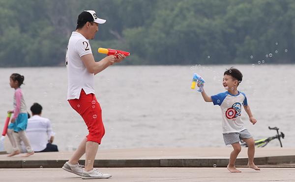 더위를 피해 서울 여의도 한강공원 물빛광장을 찾은 한 어린이가 아빠와 함께 물총 놀이를 하며 즐거워하고 있다. (사진=저작권자(c) 연합뉴스, 무단 전재-재배포 금지)