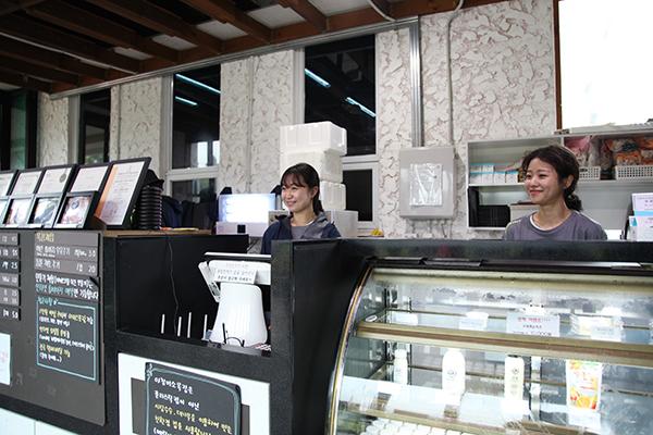 '지역주도형 청년일자리 사업'을 통해 아침미소에서 근무하는 두 사람이 카페에서 일하고 있다.