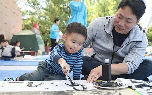 서울어린이대공원에서 열린 2018 데굴데굴 축제에서 한 어린이가 아빠와 함께 서예 체험을 하고 있다. (사진=저작권자(c) 연합뉴스, 무단 전재-재배포 금지)