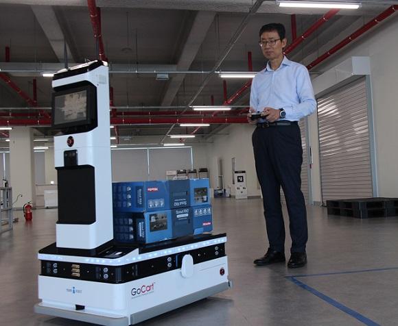 신경철 대표가 실제 물류를 적재한 자율주행 물류 배송 로봇 고카트를 조종해 시연해보이고 있다.