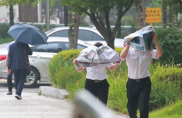 서울 지역에 비가 내리기 시작한 17일 오후 서울 서초구 서울고등법원 앞에서 법원 관계자들이 신문으로 머리를 가린 채 이동하고 있다.(사진=저작권자(c) 연합뉴스, 무단 전재-재배포 금지)