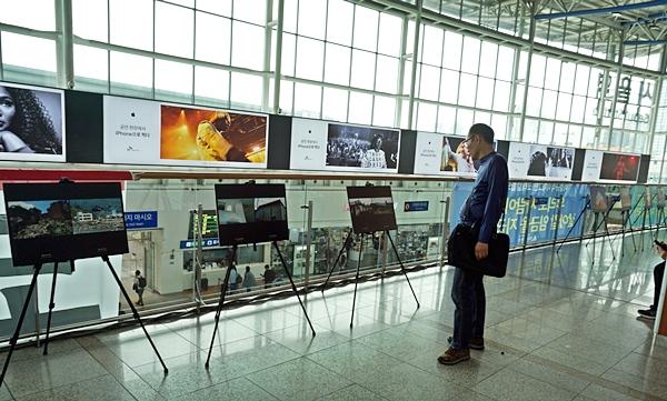 3층에 마련된 지진 사진 공모전 수상작과 우리나라 지진에 대한 사진 전시를 한 국민이 유심히 보고 있다.