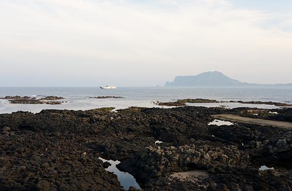 우도에서 본 성산포. 멀리 우도를 향해 오는 여객선이 보인다.