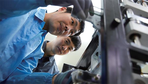 안마이크론시스템 직원들이 장비를 살펴보고 있다.