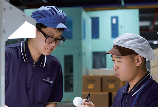우성플라테크 직원들이 제품을 살펴보며 대화를 나누고 있다.