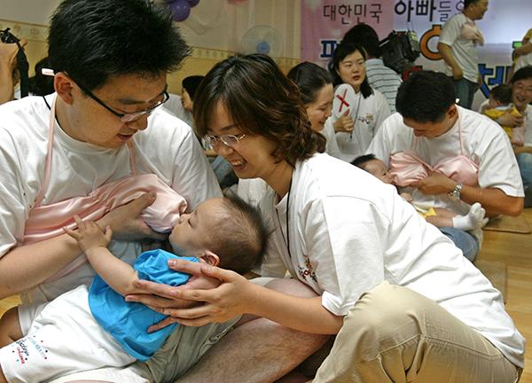 아빠들이 아이를 안고 분유만 먹여도 옥시토신 분비는 높아진다. 사진은 아빠들이 수유브래지어를 착용하고 아기에게 젖을 먹이고 있는 모습. (사진=저작권자(c) 연합뉴스, 무단 전재-재배포 금지)