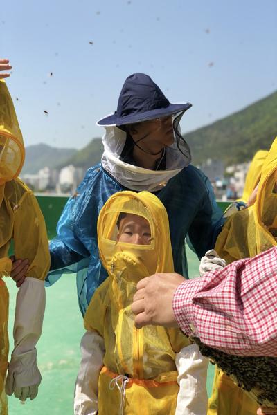 양봉장 관리를 도맡고 있는 발달장애 사원 김태웅(22)씨가 도시양봉 체험교육에 참여하는 어린이들의 안전관리를 맡고 있는 모습이다.