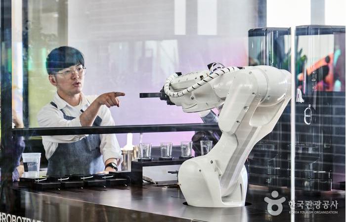 유리창을 사이에 두고 사람과 로봇 바리스타가 협업한다.