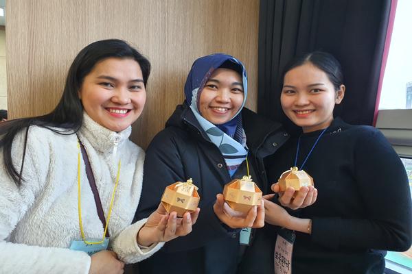 소원 복주머니를 완성한 다문화여성들이 자신이 만든 복주머니를 선보이며 밝게 웃고 있다.