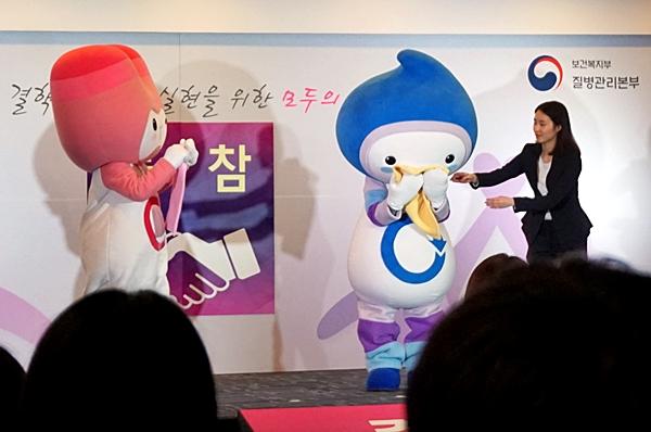 국민소통단이 만든 기침예절 캐릭터인 에띠가 행사에서 기침하는 법을 알려주고 있다.