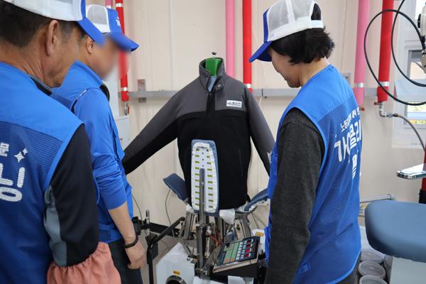 기름때 묻은 작업복을 특수세제로 세탁후 마무리 건조작업을 하는 세탁소 근로자의 모습.