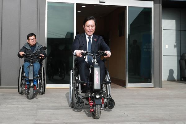 성윤모 (가운데) 산업통상자원부 장관이 지난달 경기 김포 ㈜알에스케어서비스를 방문, 수동휠체어인 전동보조키트를 탑승하고 있다. <사진=산업통상자원부 제공>