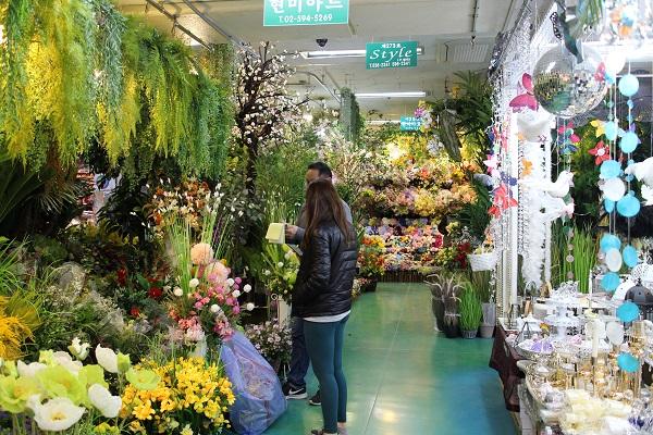 고속버스터미널 꽃 도매시장에서 사장님과 손님이 이야기하고 있다.