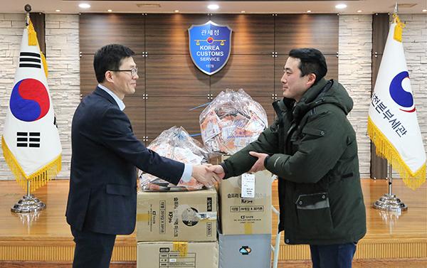 인천세관 통관지원과 양을수 과장왼쪽이 한국사회복지협의회 산하 인천 푸드마켓 유현우 사회복지사에게 마스크를 전달하고 있다.(사진=관세청)