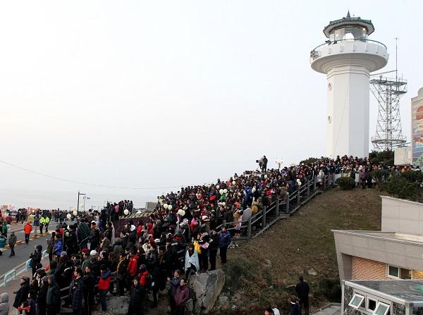 울산 간절곶 해안위 간절곶 등대 앞에 해맞이객들이 해를 기다리며 줄지어 서 있다.(사진=저작권자(c) 연합뉴스, 무단 전재-재배포 금지)