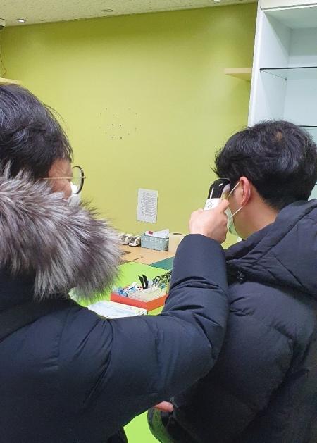 직원들이 서로 체온측정계를 통해 체온을 측정하고 있다.