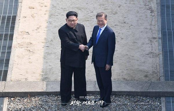 2018년 4월 27일 오전 문재인 대통령과 김정은 국무위원장이 판문점 군사분계선에서 악수를 하고 있다.2007년 10월 이후 11년 만에 이루어진 남북정상회담에서 사상 처음 북한 최고지도자가 남측 땅을 밟았고 남북 정상은 손잡고 군사분계선을 넘나들었다.