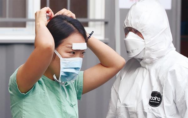 3월 5일 대구시 중구 계명대학교 대구동산병원에서 의료진이 얼굴에 반창고를 붙인 채 마스크를 쓰고 있다.│연합
