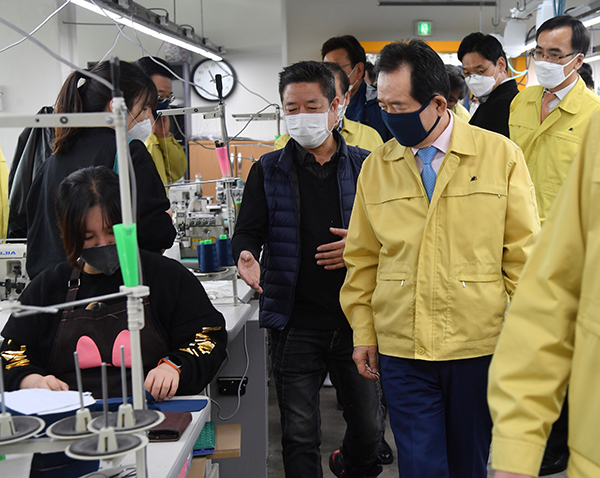 정세균 국무총리가 25일 서울 용산구 봉제공장을 방문, 필터 교체형 마스크 생산 과정을 살피고 있다.