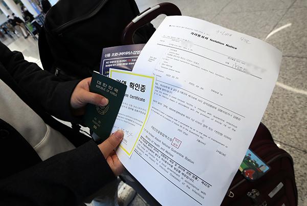 영국 런던발 입국자가 24일 오후 인천국제공항 2터미널에서 격리통지서와 검역확인증을 들고 공항 입국장을 빠져나가고 있다. (사진=저작권자(c) 연합뉴스, 무단 전재-재배포 금지)