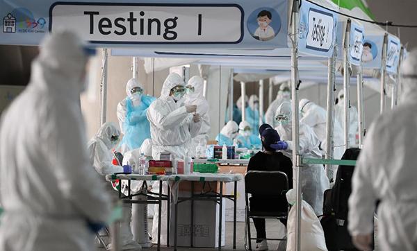 인천공항에 도착한 입국자들이 인천국제공항 제2터미널 옥외 공간에 설치된 개방형 선별진료소에서 육군 현장지원단과 의료진으로부터 코로나19 검사 관련 안내 및 검체 채취를 받고 있다.
