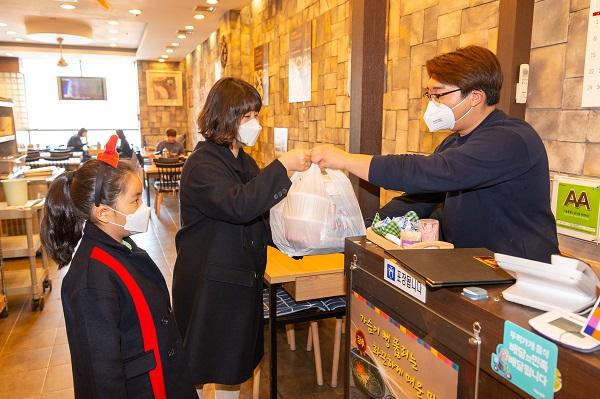착한 소비 캠페인에 동참한 양천구 지역 주민이 동네 음식점에서 선결제한 뒤 주문한 음식을 받고 있다. (사진=서울 양천구)