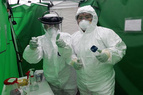 기존 선별진료소 음압텐트의 경우 환자 1명당 검사 시간이 1시간이 소요됐다. 방호복을 입고 동료 의사와 코로나19를 검사하는 안의현 의무사무관(왼쪽)의 모습.