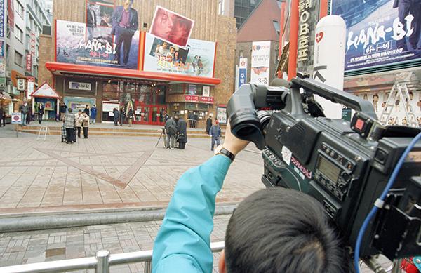 일본문화 개방 이후 1998년에 국내에 일본 영화가 처음 개봉되자 서울 시내 한 극장앞에서 일반 관람객들이 첫 개봉작인 <하나-비>의 포스터를 관심있게 살펴보고 있다. (사진=저작권자(c) 연합뉴스, 무단 전재-재배포 금지)
