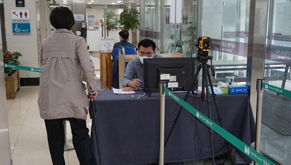 입구의 직원이 한 시민이 작성한 출입기록지에 도장을 찍어 주는 모습