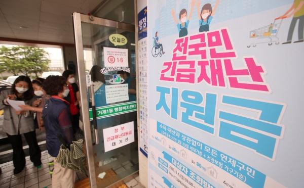 18일 오후 부산시 연제구 거제1동 주민센터를 찾은 시민들이 긴급재난지원금을 신청하고 있다.(출처=뉴스1)